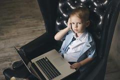 Intelligenter kleiner Kleinkindjunge mit großen Gläsern Kaffee bei der Anwendung ihres Laptops trinkend lizenzfreies stockfoto