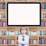 Intelligenter kleiner Student, der oben whiteboard betrachtet Lizenzfreie Stockbilder