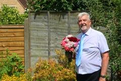 Intelligenter lächelnder Mann, der einen Blumenstrauß hält Stockfotografie