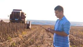 Intelligenter Landwirtschaftsmann der Landwirtarbeiten gelesen oder Analyseerntesonnenblume ein Lebensstilbericht im Tablet-Compu stock video