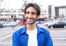 Intelligenter lateinischer Kerl in einem blauen Hemd in der Stadt Stockbild