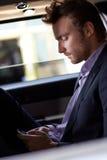 Intelligenter Mann, der auf Mobiltelefon im eleganten Auto simst Lizenzfreies Stockfoto