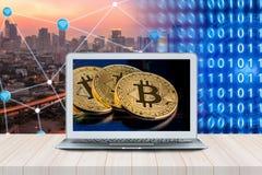 Intelligenter moderner Laptop mit Bitcoins auf Schirm auf Holztisch Stockbild