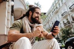 Intelligenter positiver Mann, der seinen Smartphone verwendet Lizenzfreie Stockfotos