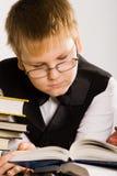 Intelligenter schauender Schulejunge, der ein Buch liest Lizenzfreies Stockbild