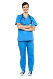 Intelligenter schauender weiblicher Doktor, Arme gefaltet Lizenzfreies Stockfoto