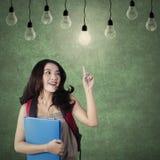 Intelligenter Student, der eine helle Glühlampe wählt Stockfotografie