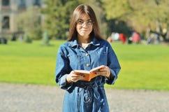 Intelligenter Student mit Gläsern ein Buch auf dem Campus lesend stockfotografie