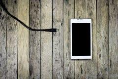 Intelligenter Telefonbedarf, eine Batterie auf hölzerner Planke aufzuladen Stockfotografie