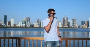 Intelligenter Telefonmann, der um Handy in an der Stadt ersucht H?bscher junger Gesch?ftsmann, der auf dem Smartphonel?cheln gl?c stock footage