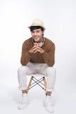 Intelligenter zufälliger asiatischer Mann gesetzt auf dem Stuhl, werfend beim Schauen von awa auf Stockfoto