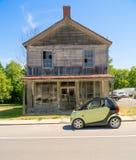 Intelligentes Auto vor altem Holzhaus. Lizenzfreie Stockfotografie
