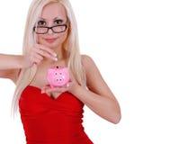Intelligentes blondes Einsparungsgeld der jungen Frau in der piggy Querneigung getrennt Lizenzfreie Stockfotografie