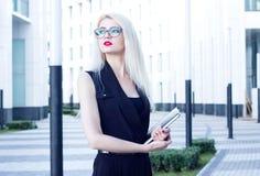 Intelligentes blondes mit den roten Lippen und Notizbuch untersucht den Abstand auf dem Hintergrund des Geschäftszentrums Lizenzfreies Stockfoto