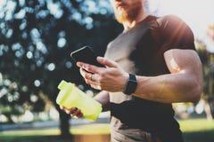 Intelligentes Eignungskonzept des Trainings Junger muskulöser Athlet, der Training programm auf Smartphoneanwendung nach perfekte Lizenzfreies Stockbild