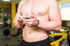 Intelligentes Eignungskonzept des Trainings Nahaufnahme des jungen muskulösen Athleten, der Trainingskurs über Smartphoneanwendun Stockfotos