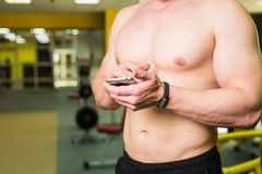 Intelligentes Eignungskonzept des Trainings Nahaufnahme des jungen muskulösen Athleten, der Trainingskurs über Smartphoneanwendun Lizenzfreie Stockfotos