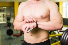 Intelligentes Eignungskonzept des Trainings Nahaufnahme des jungen muskulösen Athleten, der Trainingskurs über Smartphoneanwendun Lizenzfreie Stockfotografie