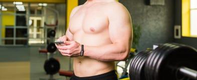 Intelligentes Eignungskonzept des Trainings Nahaufnahme des jungen muskulösen Athleten, der Trainingskurs über Smartphoneanwendun Stockbilder