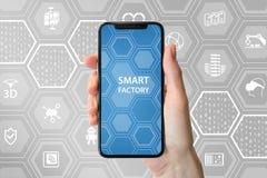 Intelligentes Fabrikkonzept mit Symbolen Hand, die freies intelligentes Telefon der Einfassung hält stockfotos