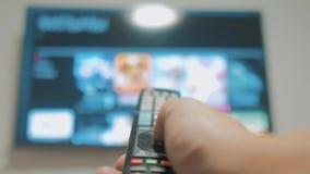 Intelligentes Fernsehen mit Apps und der Lebensstilhand Männliche Hand, die weg den intelligenten Lebensstil der Fernbedienungsdr stock video