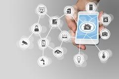 Intelligentes Hauptkonzept mit der Hand, die modernes intelligentes Telefon hält, um Haushaltsgeräte zu steuern Lizenzfreie Stockfotografie