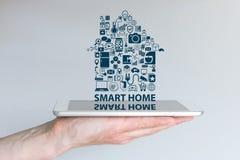 Intelligentes Hausautomationskonzept Hintergrund mit der Hand, die intelligentes Telefon hält und Text und Ikonen schwimmt Lizenzfreie Stockbilder