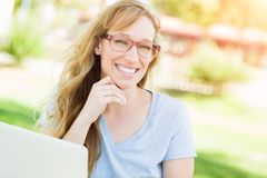 Intelligentes jugendlich Mädchen trägt Gläser draußen auf ihrem Laptop Lizenzfreie Stockfotos