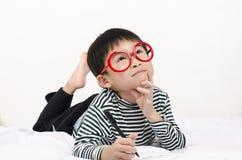 Intelligentes Kind, das auf Bett liegt Stockbilder