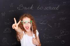 Intelligentes Kind mit den roten Gläsern, die Gestenfrieden oder Sieg ha zeigen Lizenzfreie Stockbilder