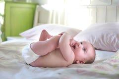Intelligentes Kind sitzt auf einem Bett in einem hellen Raum Stockfoto