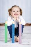 Intelligentes kleines Mädchen, das große Zeichenstifte hält Stockbilder