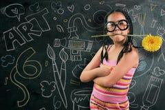 Intelligentes kleines Mädchen, das vor einer Tafel lächelt Lizenzfreie Stockbilder