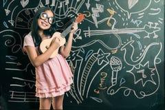 Intelligentes kleines Mädchen, das vor einer Tafel lächelt Stockbilder