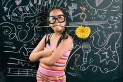Intelligentes kleines Mädchen, das vor einer Tafel lächelt Lizenzfreies Stockfoto