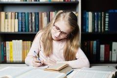 Intelligentes kleines Mädchen mit Gläsern schreibend auf Buch, stockbild
