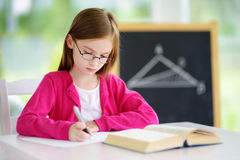Intelligentes kleines Schulmädchen mit Stift und Bücher, die einen Test in ein Klassenzimmer schreiben Stockbild