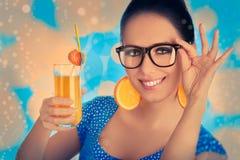 Intelligentes Mädchen mit Orangensaft und orange Scheibe Earr Stockfotografie