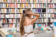 Intelligentes Mädchenkind gedankenverloren viele Bücher in einer Buchhandlung Lizenzfreie Stockbilder