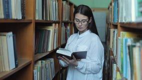Intelligentes Schauen und schönes junges Mädchen im weißen Hemd und in den Gläsern in der Collagenschulbibliothek, die Buch vorwä stock video