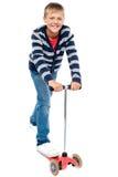 Intelligentes schauendes Kindreiten auf seiner zippy Schleife Stockfoto