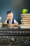 Intelligentes Schulmädchen, das ein Buch an der Bibliothek liest Lizenzfreie Stockbilder