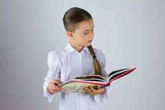 Intelligentes Schulmädchen, das ein Buch liest Stockbild
