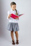 Intelligentes Schulmädchen, das ein Buch liest Stockfotografie