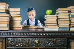 Intelligentes Schulmädchen, das ein Buch an der Bibliothek liest Lizenzfreies Stockfoto
