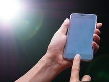 intelligentes Telefon auf Blendenfleck der Quelle des grellen Lichts in der Dunkelheit Lizenzfreies Stockbild