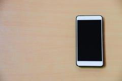 Intelligentes Telefon auf dem hölzernen Schreibtischhintergrund Stockfoto