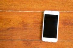 Intelligentes Telefon auf hölzernem Hintergrund Stockbilder