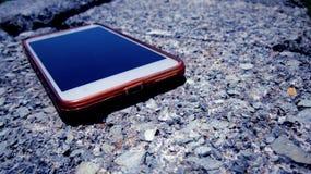 Intelligentes Telefon auf kleinen Felsen auf Zement-Ziegelstein Lizenzfreie Stockfotos