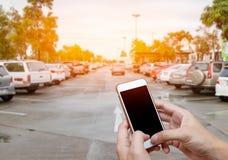 Intelligentes Telefon, das leeren Bildschirm in der Mannhand mit UnschärfeParkplatz zeigt lizenzfreies stockbild